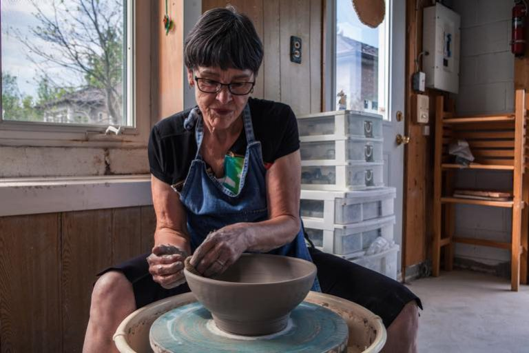 An artist works a potter's wheel along the Arts & Heritage trail